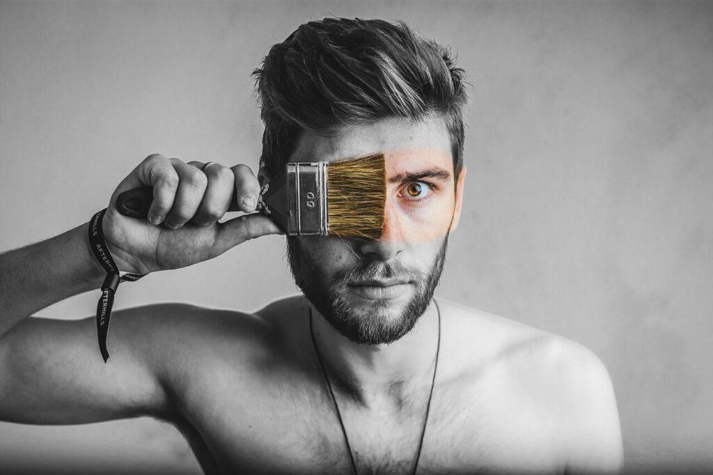 una fotografía de un Hombre en blanco y negro pintándose la cara con una brocha en señal de poder