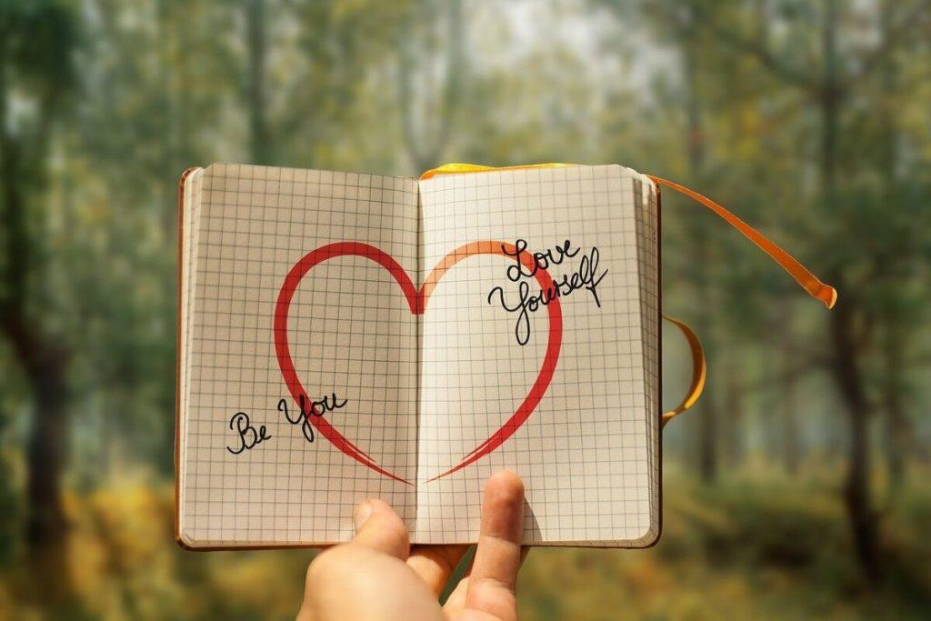Agenda abierta dibujado un corazón y escrito: be you y love  yourseff
