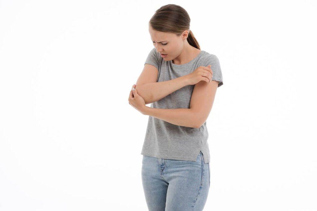 Mujer tocándose el codo, por dolor a las articulaciones.png